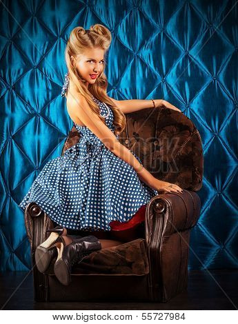 Charming pin-up woman with retro hairstyle and make-up sitting in the armchair over vintage background. poster