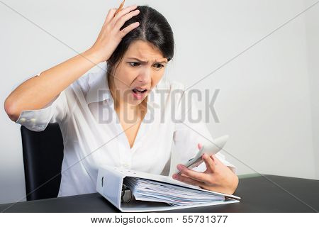 Businesswoman Looking At Her Calculator In Horror