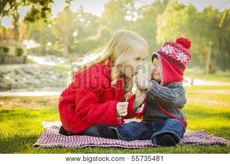 Little Girl with Her Baby Brother Wearing Winter Coats and Hats Sharing a Lollipop Outdoors at the Park.  poster