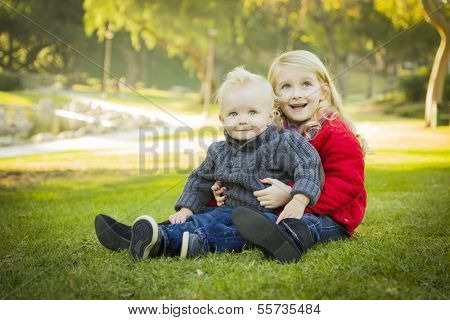 Little Girl with Her Baby Brother Wearing Winter Coats Outdoors Sitting at the Park.
