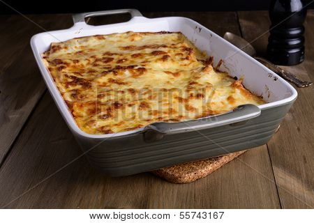 Lasagna In A Serving Plate With Cheese On Top On An Old Wood Table