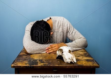 Sad Man With Skull At Desk