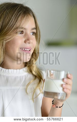 Cute litle girl holding glass of milk