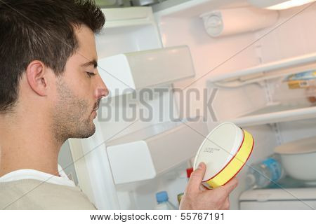 Man looking at expiry date of fresh product