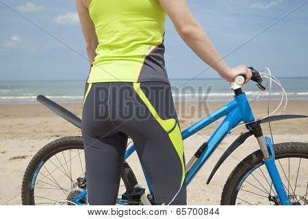 Girl In A Green Jumpsuit With A Blue Bicycle On The Beach