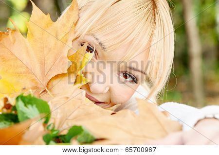 Young Blonde Behind The Leaves