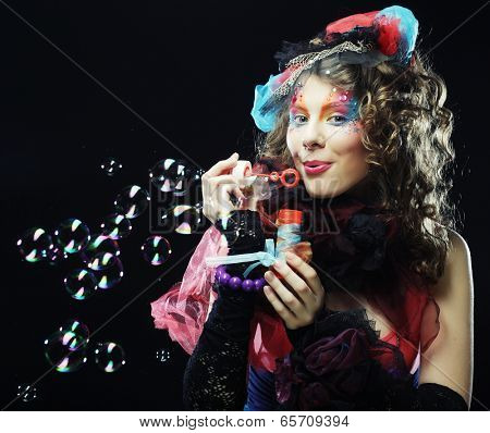 Fashion model with creative make-up blowing soap bubbles. Doll style.
