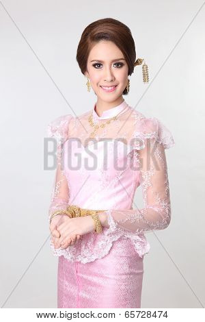 elegant fashion brunette woman posing with creative chignon hair-style and wearing pink thai dress