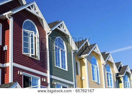 A row of colorful new townhouses or condominiums. poster