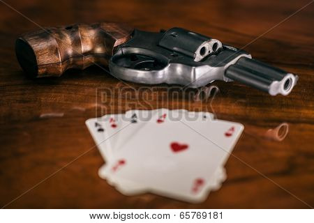 Risky gambling concept. Gun and four aces cards on wooden table. poster