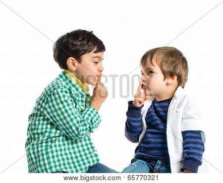 Kids doing silence gesture over white background poster