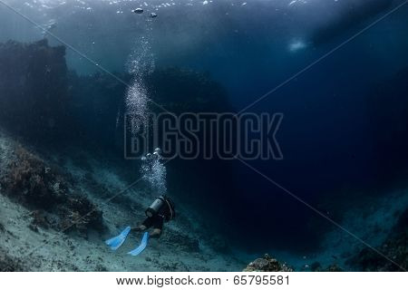 Scuba diver moving towards profound darkness