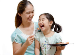 Asian mother feeding sausage to her daughter