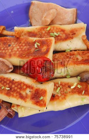 russian food - meat wrapped in a pancake with red hot pepper  and pickled mushrooms served on blue plate isolated over white background high resolution hidef