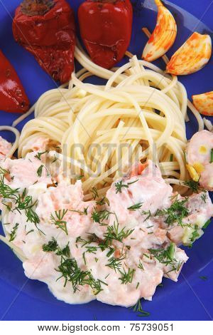 fresh rose wild salmon baked in cream cheese sauce with italian pasta and red hot pepper on blue plate isolated over white background high resolution hidef