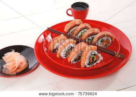 japanese cuisine onigiri sashimi inside out sushi rolls with ginger and sake cup on red plate over white wooden table high resolution hidef