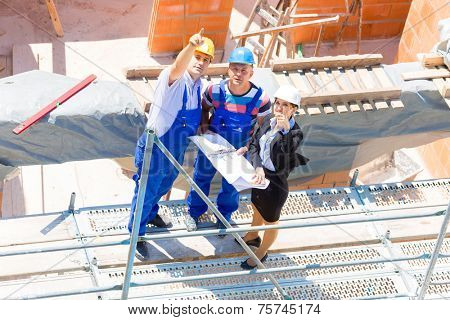 Construction site Team or architect and builder or worker with helmets discuss on a scaffold construction plan or blueprint or checklist