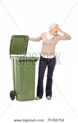 Vertical shot of a woman opening a stinky trash can isolated on white background