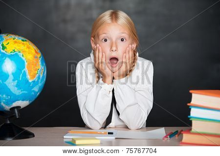 Surprised shcool girl in classroom