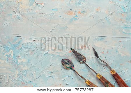 Three Palette Knifes On Artist Canvas With Oil Paint