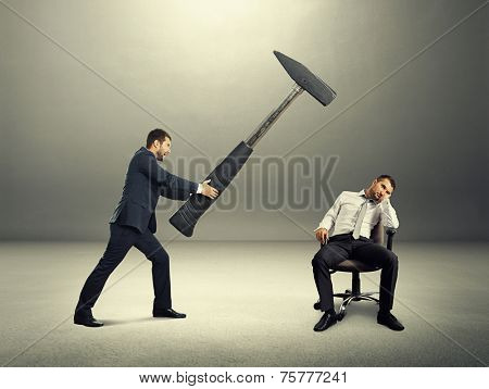 displeased boss holding big hammer and screaming at lazy worker. photo in the dark room