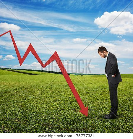 displeased businessman looking at red downturn graph. photo at outdoor