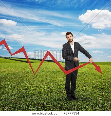 sad broker holding and pointing at falling down graph. photo at outdoor