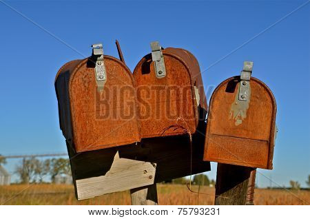 Three rusty old mail boxes