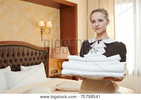 Hotel service. female housekeeping worker with towels and bedclothes at inn room