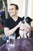 Caucasian man sitting at a street cafe table with his pet dog on his lap poster