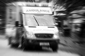 Black and white image of ambulance traveling through city center with zoom effect poster