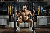 very brawny guy bodybuilder execute exercise squatting with weight in gym poster