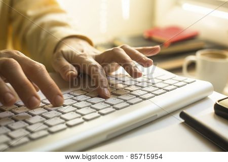 Women's fingers typing on laptop keyboard close-up.