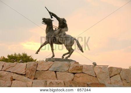 rider on horseback against pink sunset