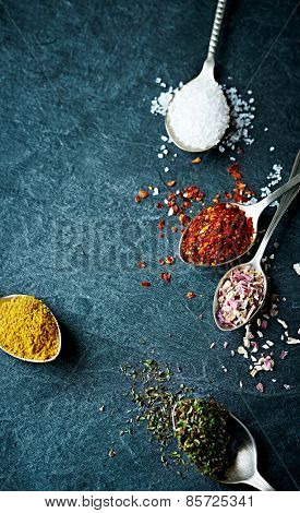Assorted natural spices on old spoons