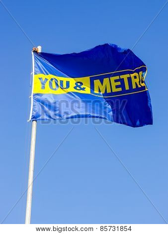 The Promo Flag Of Metro Store Over Blue Sky