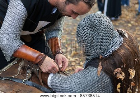 ZAGREB, CROATIA - OCTOBER 07, 2012: Squire helping the knight with his armor at