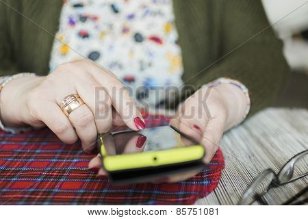hand of senior woman with yellow smartphone