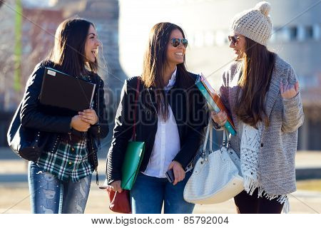 Three Students Girls Walking In The Campus Of University.