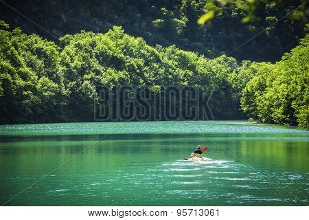 Lonely Adventurer Kayaking at the Beautiful Lake with Tranquil Panorama View. poster