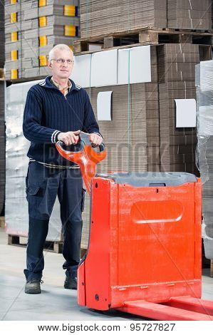 Full length portrait of confident male worker standing with handtruck at warehouse