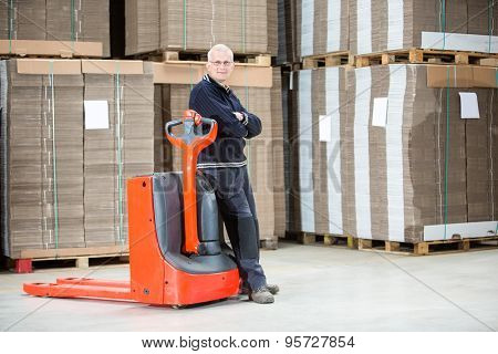 Full length portrait of confident worker standing arms crossed while leaning on handtruck at warehouse