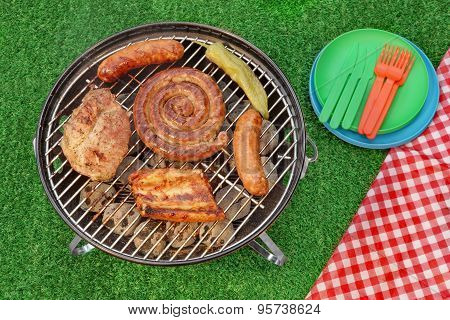 Bbq Portable Grill With Assorted Meat And Picnic Red Blanket