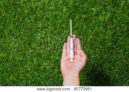 Human hand holding syringe close up