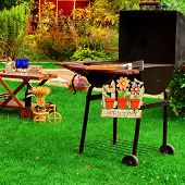 Garden Wooden Furniture Picnic Hamper Basket BBQ Grill Sign Welcome Wine Glasses On The Table Plants Trees and House In The Background. Backyard BBQ Grill Party Or Picnic Concept poster