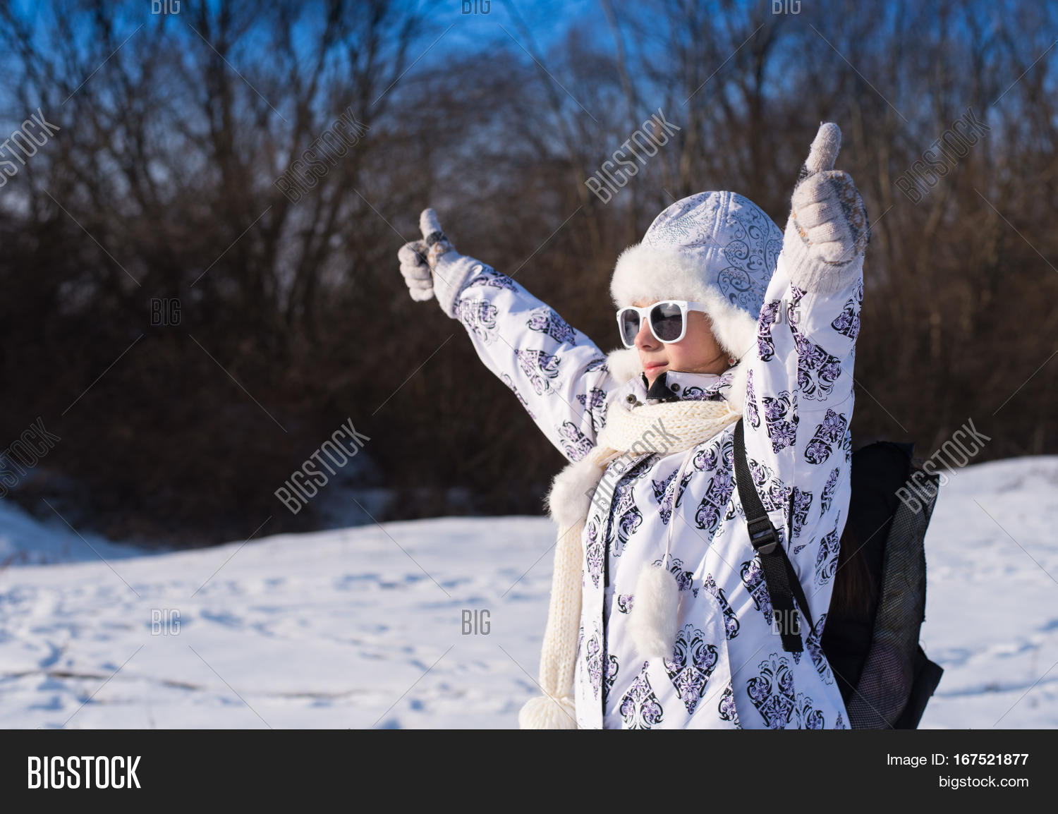 0739ad7b0074 Funny little girl in sunglasses in winter a sunny day. Thumb up sign.  Caucasian