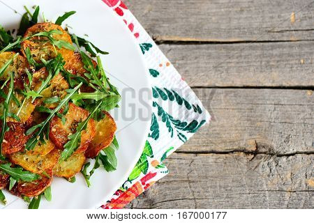 Spicy potatoes with arugula on a plate and wooden background with copy space for text. Fried potatoes with fresh arugula and dry spices. Fast and tasty vegetable side dish. Top view