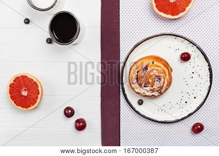 Attractive reason to get out of bed. Fresh sweet homemade bun with berries lying on a plate surrounded by barriers and grapefruits spreading all over white wooden table