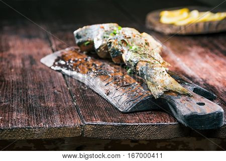 Baked salmon fish with tarragon and sesame on wooden board. Selective focus