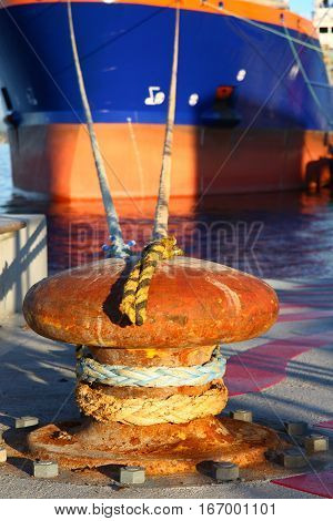 Close up of a port bollard with commercial freight ship mooring lines tied to keep the ship at anchor.